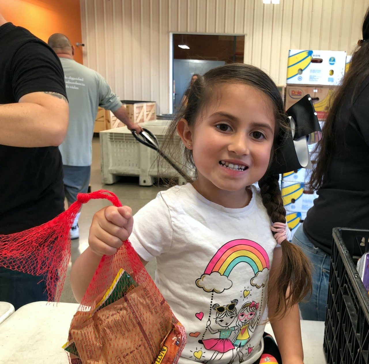 Child holds student snack bag at Community Food Bank of San Benito County