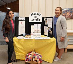 Representatives from Jovenes de Antano standing at display table during wellnes fair at Food Bank of San Benito County
