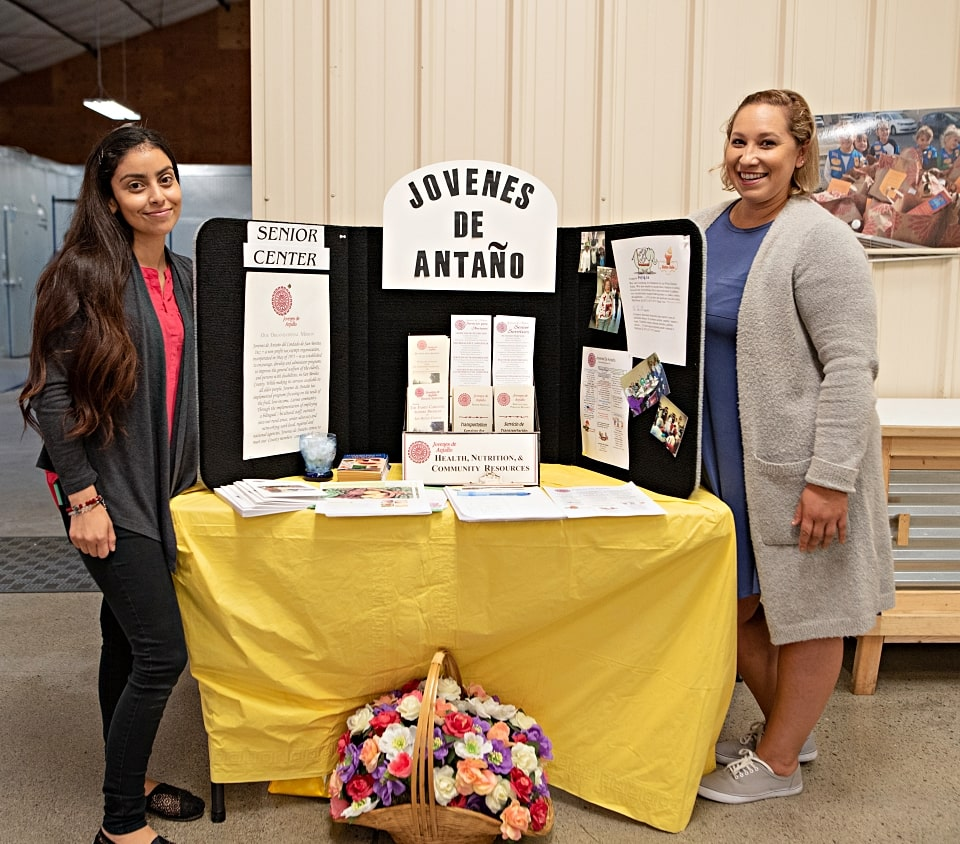 Representatives from Jovenes de Antano standing at display table during wellnes fair at Food Bank of San Benito County